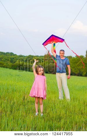 Dad and daughter fly a kite in a field.
