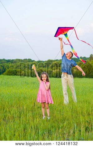 Dad playing with his daughter. Little girl and dad flying kite.