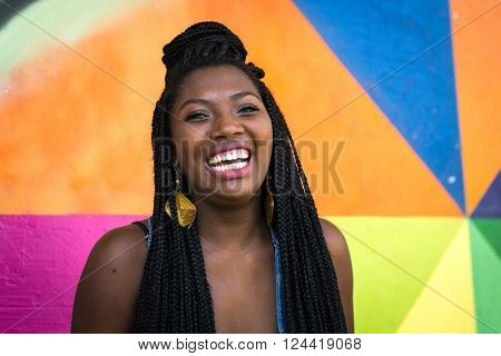 Portrait of Young Afro Brazilian woman smiling on colorful background