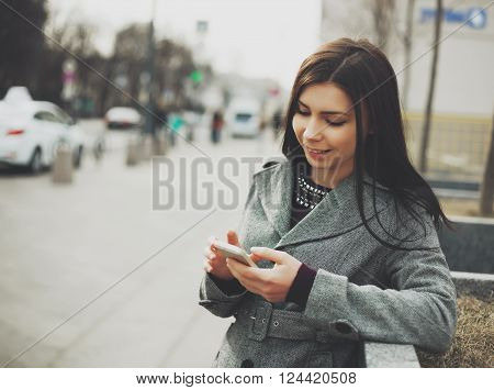 Young brunette girl using her moder touch screen smart phone outdoors with a friendly smile
