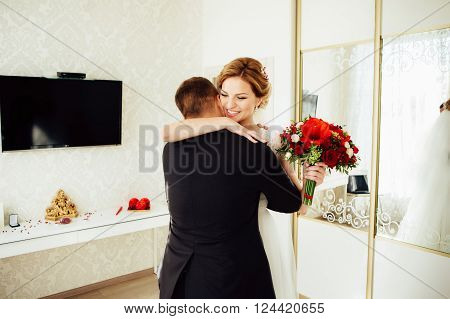Handsome groom is seeing first the beauty bride in the morning. Meeting of a wedding couple. Beautiful model girl in white dress and in lace veil. Man in suit. Female and male portrait. Woman and guy