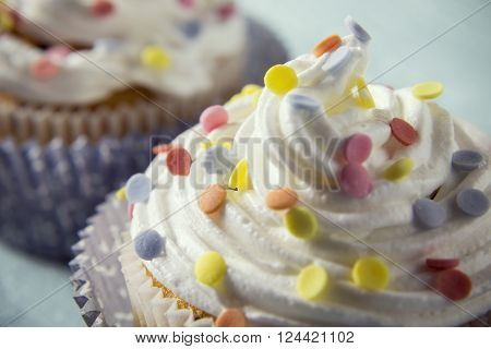 Close up of a cream with colorful sprinkles on a cupcake