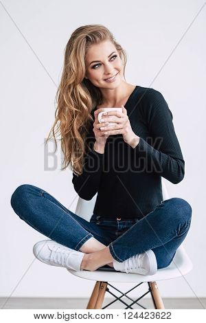 Coffee lover. Beautiful young woman holding coffee cup and looking away with smile while sitting on chair in lotus position against white background
