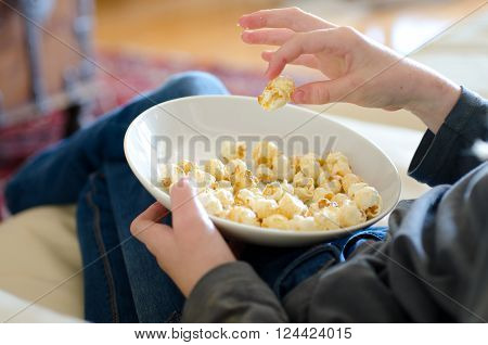 child eating popcorn while watching a film maybe