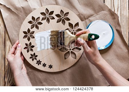 Master Class. Watch handmade. Step by step instructions for the manufacture of clocks. Do it yourself. Hands with paint brush watch white acrylic paint. Kraft paper on a wooden background.