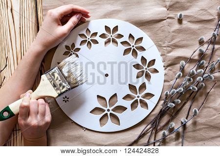 Master Class. Watch handmade. Step by step instructions for the manufacture of clocks. Hands with paint brush base clock of white paint. Willow branches against the backdrop of kraft paper