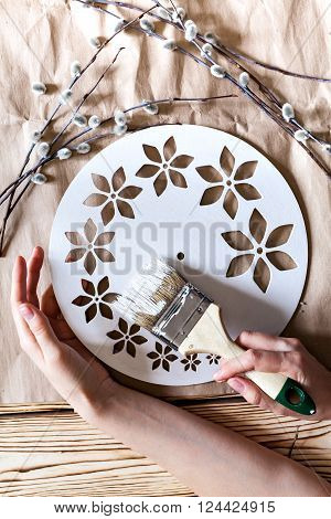 Master Class. Watch handmade. Hands with paint brush base clock of white paint. Step by step instructions for the manufacture of clocks.  Willow branches against the backdrop of kraft paper