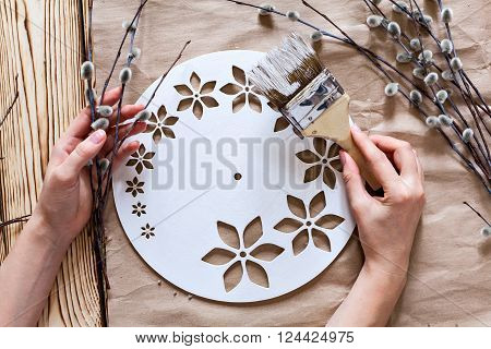 Step by step instructions for the manufacture of clocks. Master Class. Watch handmade.  Hands with paint brush base clock of white paint. Willow branches against the backdrop of kraft paper