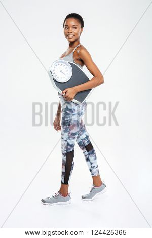 Full legth portrait of a happy fitness afro american woman holding weighing machine isolated on a white background
