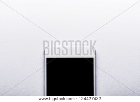 Smart phone laid on white office desk, flat lay, copy space