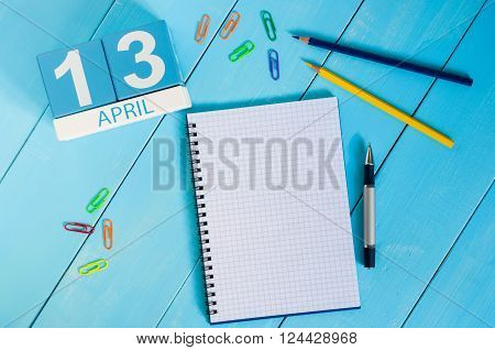 April 13th. Image of april 13 wooden color calendar on blue background.  Spring day, empty space for text. World Rock-n-roll Day.