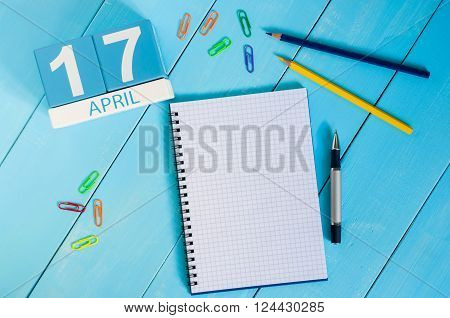 April 17th. Image of april 17 wooden color calendar on blue background.  Spring day, empty space for text. Tax Deadline.
