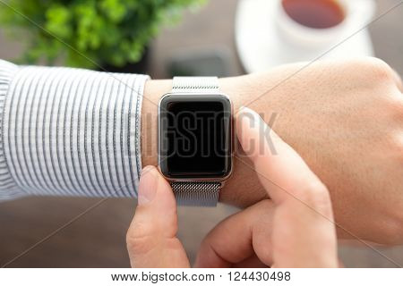 Man hands with smart watch over the table in the office