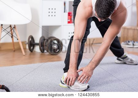 Muscular active young man having training at home