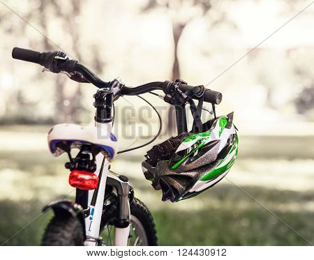 Safe bicycle helmet hanging on the handgrip