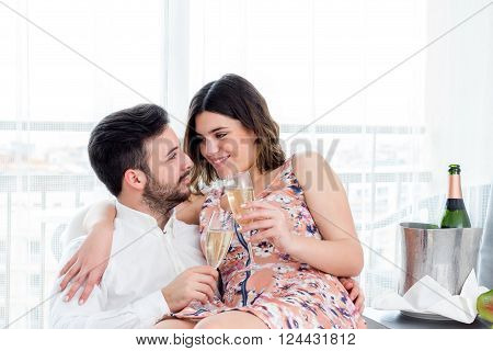 Close up portrait of young happy couple celebrating weekend getaway in hotel suite with champagne.