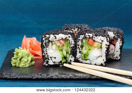 Japan black tobiko rolls with cream cheese and cucumber served with chopsticks ginger and wasabi on black board closeup
