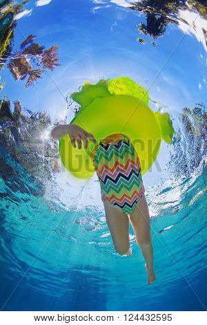 Funny underwater photo of baby girl swimming with fun on inflatable frog tube in clear aqua park pool. Healthy family lifestyle children outdoor water sports activity with parents on summer holidays.