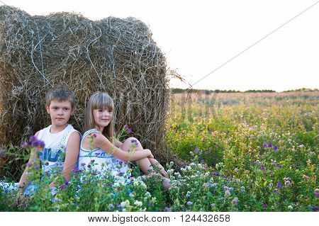 The boy and the girl sit on a glade about a big haystack