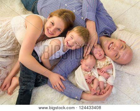 Happy parents posing with their newborn identical twins and toddler brother
