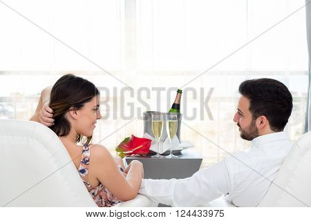 Close up portrait of young honeymoon couple in hotel suite celebrating with champagne.