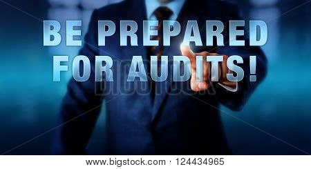 Male Chief Information Security Officer is touching the phrase BE PREPARED FOR AUDITS! on a visual screen. Business challenge metaphor and information technology concept for audit-readiness.