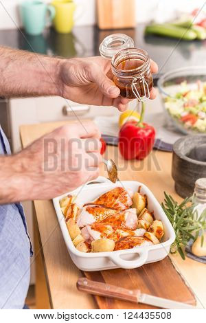 Man's or chef's hands preparing dinner (chicken drumsticks with potatoes) in a roasting dish - close up. Cooking - kitchen interior as background food ingredients on table.