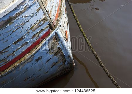 Wooden bow of an old clinker built fishing boat with flaking paint and mooring rope