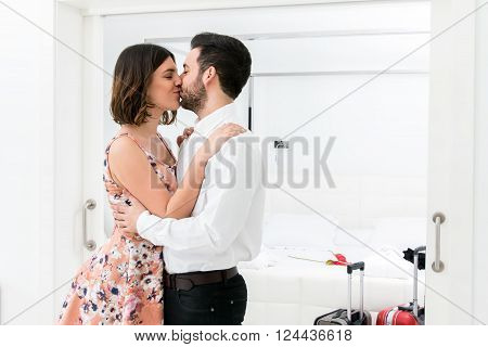 Close up portrait of romantic kiss in hotel suite.