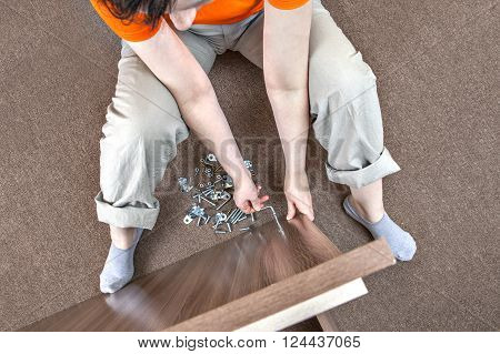 Caucasian woman housewife mounts wooden furniture at home.