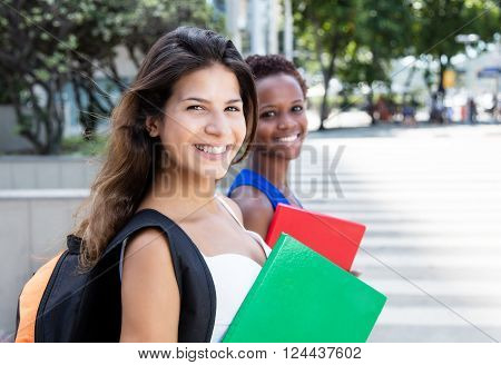 Laughing caucasian female student with african american girlfriend