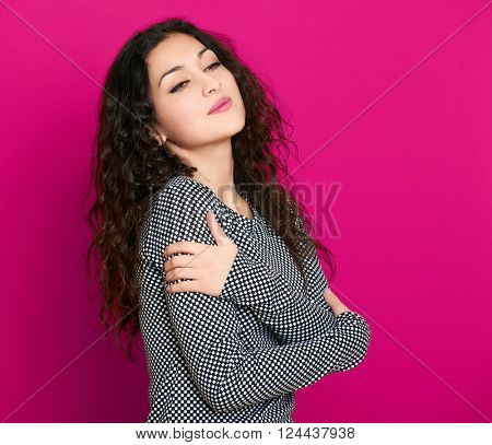 girl glamour portrait on pink background, long curly hair