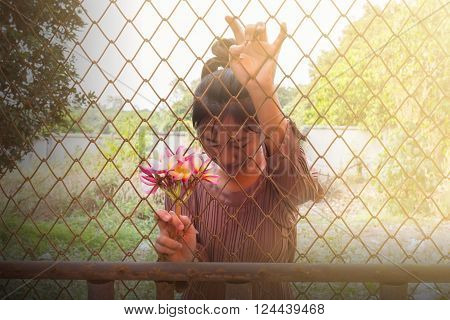 Women and bunch of pink flowers frangipani in hand behind iron bar
