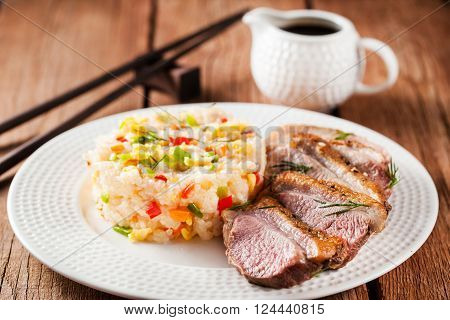 Asian style food - fried duck breast and jasmine rice with vegetables and eggs