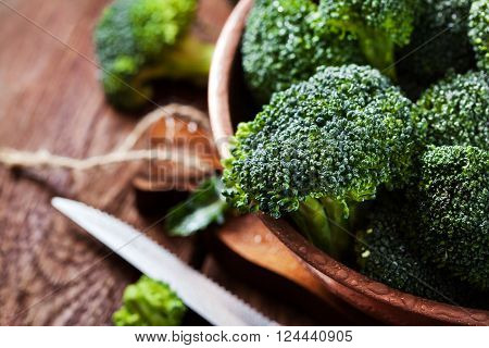 Fresh raw green broccoli in bowl on rustic wooden background