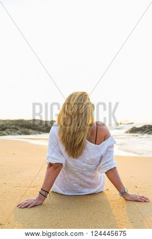 young woman is sitting on beach at sunrise in Khao Lak Thailand