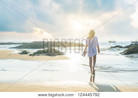 woman walking on sand beach at golden hour