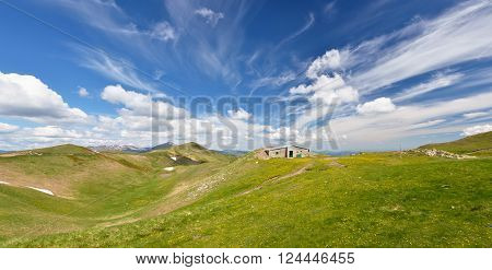 isolated mountain refuge under amazing sky in summer