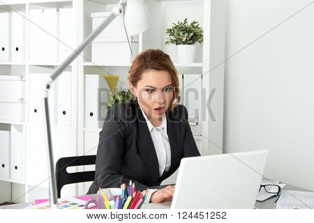 Portrait of surprised businesswoman looking at her laptop screen. Impressed woman. Shocking, unexpected, breaking news, problems, failure, computer virus or deadline concept.
