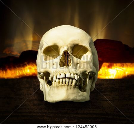 Human skull on a background of a burning fireplace