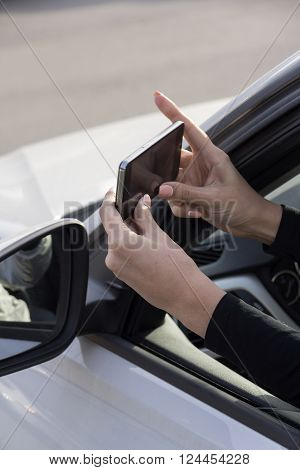a girl takes pictures on a cell phone from the car window