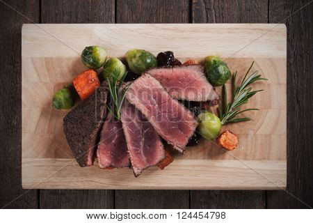 Medium rare beef steak with carrot and brussel sprout on wooden board