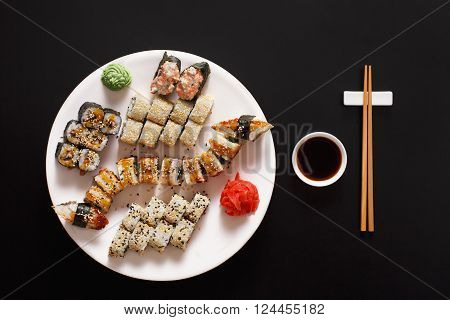Japanese food restaurant, sushi maki gunkan roll plate or platter set. Free, copy space, chopsticks, ginger and wasabi. Sushi at white round plate, rustic wood background. Top view with soy sauce