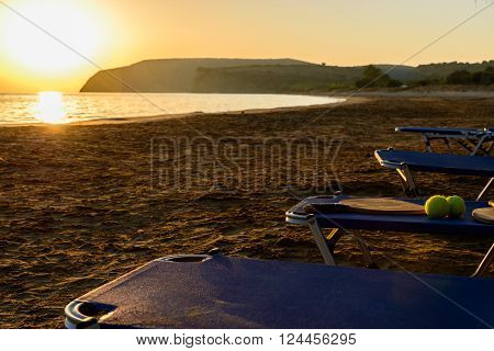 Racket and tennis balls on a chaise longue chair at a sandy beach during sunset