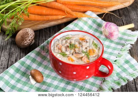 Tasty creamy cheese mushroom soup with spring carrots and veggies decorated with dill in a red cup on an old rustic table top view