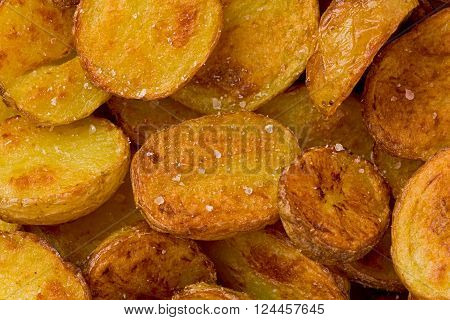 Background texture of roasted potatoes with salt crystals.