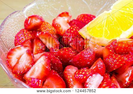 cut strawberries macerated in lemon in a glass cup