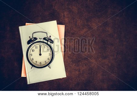Vintage alarm clock reminder symbol on noon midnight hour on wooden desktop background