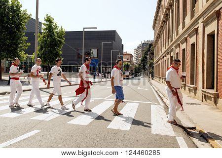 Spain Navarra Pamplona 10 July 2015 S Firmino fiesta guys in typical dress for the feast walking in the street