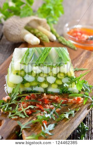 Asparagus jelly with fresh white and green asparagus and chives, served with red pepper vinaigrette